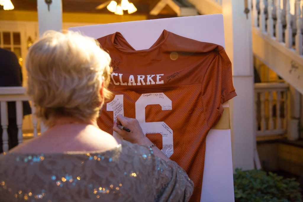 Football Jersey Guestbook Signing | The Courtyard at Lake Lucerne Classic Purple & Orange Wedding Football Texas Longhorns Sports Lake Lucerne Courtyard Anna Christine Events Orlando Kathy Thomas Photography