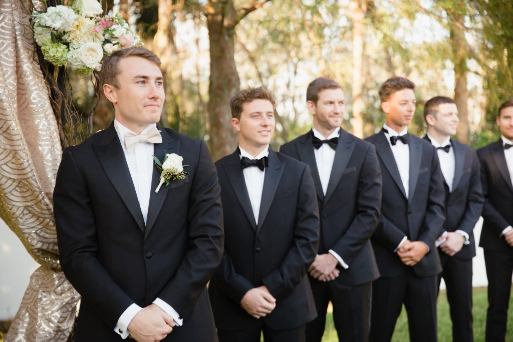 Groom & Groomsmen at Altar Arbor Outdoor Ceremony | Travel Inspired Themed Glamorous Gold & White Wedding Luxmore Grande Estate Anna Christine Events Justin DeMutiis Photography